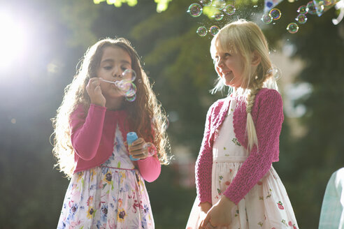 Two cute girls blowing bubbles in sunlit garden - CUF31810