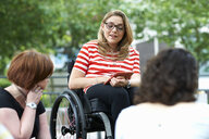 Female student in wheelchair chatting to friends on college campus - CUF31828