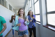 Students running down hallway, laughing - CUF31849