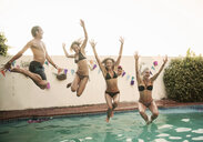 Mid adult man and three young women jumping into swimming pool at poolside party - CUF32166