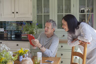 Senior couple in kitchen, looking at digital tablet - CUF32172