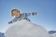 Young boy leaning over pile of snow, low angle view - ISF09887