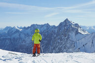 Young boy at edge of mountain, ready to ski down, rear view - ISF10025