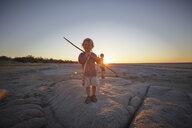 Portrait of young boy standing on rock, holding spear, sunset, Gweta, makgadikgadi, Botswana - ISF10091