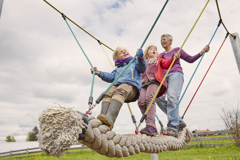 Grandmother and grandchildren playing on rope bridge, low angle view - ISF10094