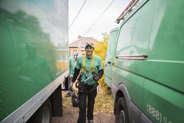 Solar panel installation worker walking in between truck and van - ISF10121