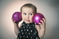 Little girl with pink christmas baubles - ISF10124