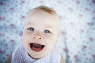 Portrait of smiling baby girl laying on mat - ISF10154