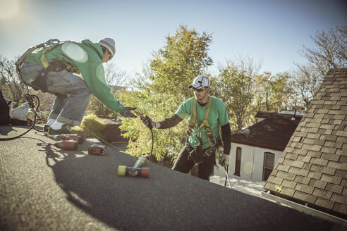 Solar panel installation crew members on roof of house - ISF10220
