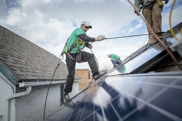 Construction crew installing solar panels on a house - ISF10229
