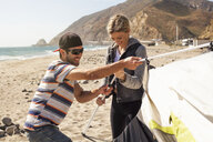 Couple setting up tent on beach, Malibu, California, USA - ISF10238