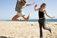 Girlfriends jumping in mid air on beach, Malibu, California, USA - ISF10241