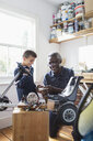 Grandfather and grandson assembling go-cart in garage - CAIF20690