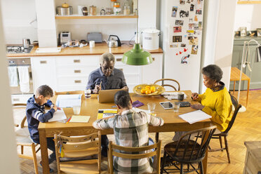 Grandparents at dining table with grandchildren doing homework - CAIF20693
