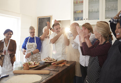 Chef and active senior friends clapping in pizza cooking class - CAIF20711