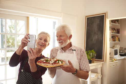 Smiling, confident senior couple taking selfie with pizza at cooking class - CAIF20717