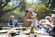 Friends toasting affectionate senior couple hugging at sunny garden party - CAIF20729
