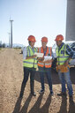 Engineer and workers using digital tablet at wind turbine power plant - CAIF20756