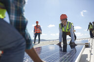 Engineers lifting solar panel at sunny power plant - CAIF20765