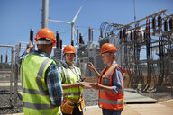Engineers with digital tablet at sunny power plant - CAIF20771