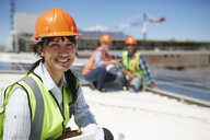 Portrait smiling, confident female engineer at sunny power plant - CAIF20783