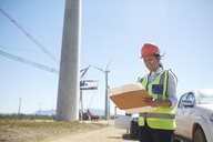 Smiling female engineer with blueprint at sunny wind turbine power plant - CAIF20786