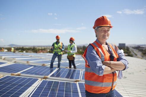 Portrait confident female engineer at sunny solar power plant - CAIF20792