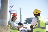 Engineers reviewing blueprints at truck at sunny wind turbine power plant - CAIF20798