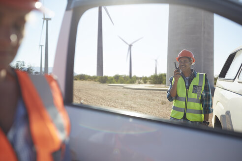 Smiling engineer using walkie-talkie at truck at sunny wind turbine power plant - CAIF20801