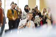 Conference audience clapping for smiling female speaker with microphone - CAIF20852