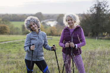 Portrait confident active senior women hikers with poles in rural field - CAIF20927
