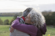 Affectionate senior couple hugging in field - CAIF20930