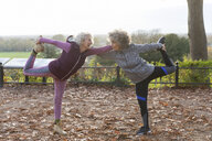 Active senior women friends stretching in autumn park - CAIF20936