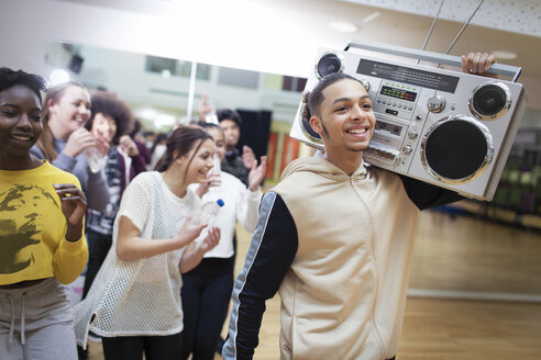 Enthusiastic, cool teenage boy with boom box in dance class studio - CAIF20939