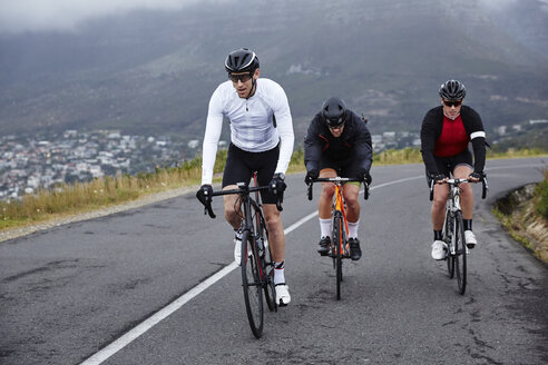 Dedicated male cyclists cycling on uphill road - CAIF20951