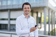 Portrait of smiling businessman with cell phone in the city - DIGF04654