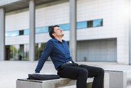 Businessman sitting outdoors leaning back - DIGF04663