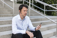 Businessman with headset and cellphone sitting on stairs - DIGF04678