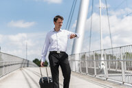 Businessman with rolling suitcase on a bridge checking the time - DIGF04681