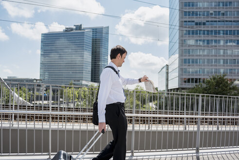 Businessman with rolling suitcase on a bridge checking the time - DIGF04684