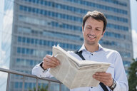 Smiling businessman reading newspaper in the city - DIGF04687