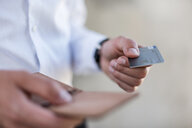 Close-up of businessman holding credit card - DIGF04702