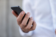 Close-up of businessman holding cell phone - DIGF04705