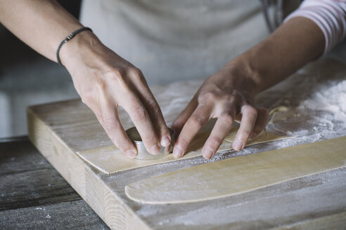Woman preparing ravioli, pasta dough cutting out on pastry board - ALBF00500