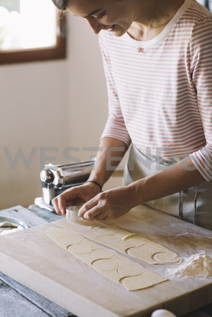 Woman preparing ravioli, pasta dough cutting out on pastry board - ALBF00509