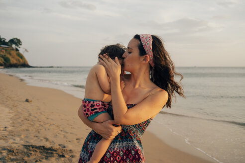 Thailand, Krabi, Koh Lanta, Mother with little daughter on her shoulders on the beach at sunset - GEMF02078