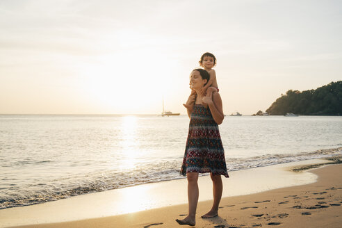 Thailand, Krabi, Koh Lanta, Mother with little daughter on her shoulders on the beach at sunset - GEMF02081