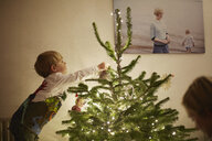Young boy putting lights onto christmas tree - CUF32437