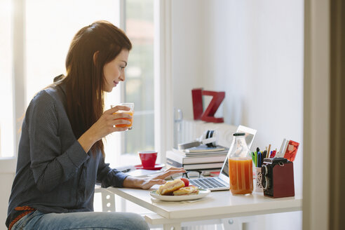 Young woman using laptop while breakfasting - CUF32452