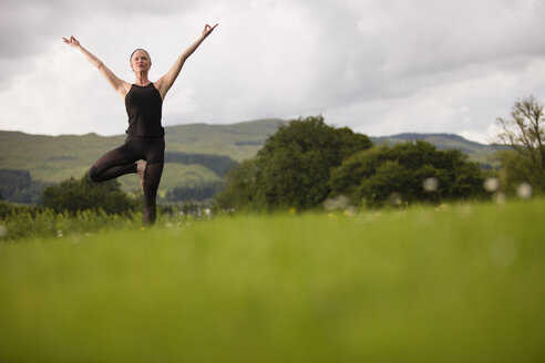 Mature woman practicing yoga tree pose in field - CUF32626